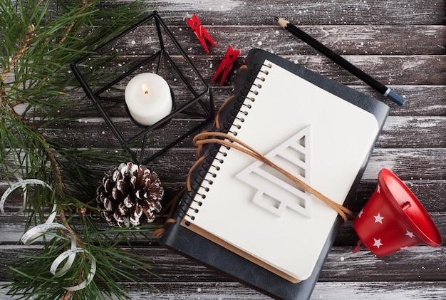 Árvore de natal, caderno aberto vazio e decoração de natal vermelha