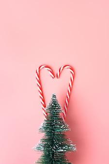 Árvore de natal com bastão de doces pendurado na parede rosa pastel