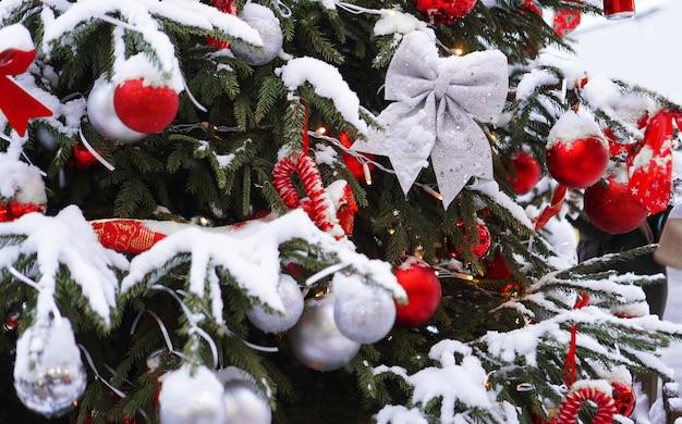 Árvore de natal com bolas vermelhas e decoração sob a neve
