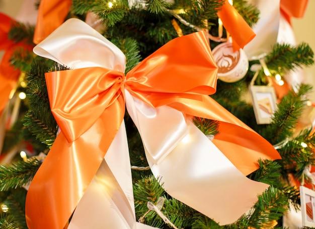 Árvore de natal com bolas vermelhas. fundo de comemoração de ano novo. foto closeup de árvore de natal decorada com laços brancos e laranja