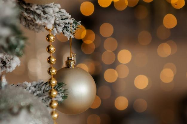 Árvore de natal com brinquedos e neve decorativa por um feliz ano novo em plano de fundo de bokee. fundo dourado de natal