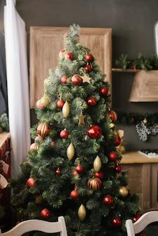 Árvore de natal com brinquedos vermelhos e dourados na sala de jantar da casa
