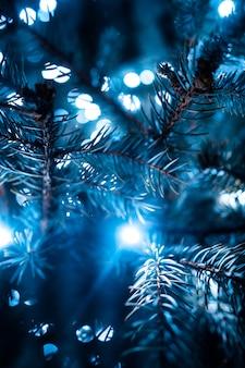 Árvore de natal com cones em uma rua da cidade iluminada com uma guirlanda.