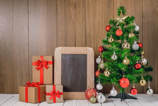 Árvore de natal com enfeites de bolas coloridas e caixas de presente com lousa