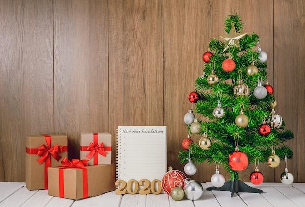 Árvore de natal com enfeites de bolas coloridas e caixas de presente com notebook