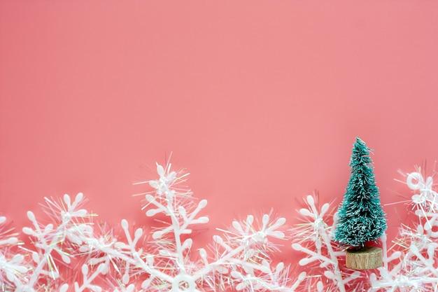 Árvore de natal com enfeites de floco de neve no fundo rosa para o dia de natal e feriados conce