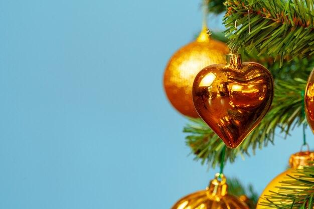 Árvore de natal com enfeites dourados close-up em azul