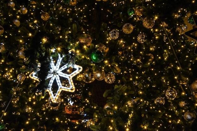 Árvore de natal com floco de neve leve e bolas à noite