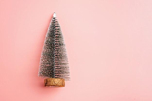 Árvore de natal com fundo rosa pastel de neve conceito mínimo de férias ano novo co simples