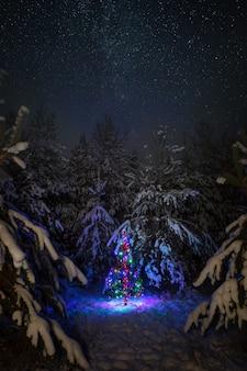 Árvore de natal com guirlandas em uma superfície do céu noturno e a via láctea na floresta de inverno