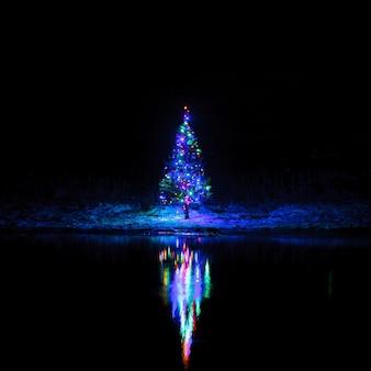 Árvore de natal com guirlandas em uma superfície do céu noturno refletida no rio