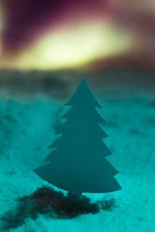 Árvore de natal com neve e aurore borealis