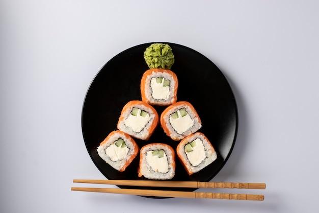Árvore de natal comestível feita de sushi de salmão com queijo da filadélfia na placa preta sobre um fundo branco. festa de ano novo. vista do topo
