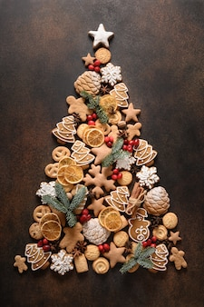 Árvore de natal criativa de biscoitos variados, estrelas de anis de canela, bagas, lascas de laranja, abeto