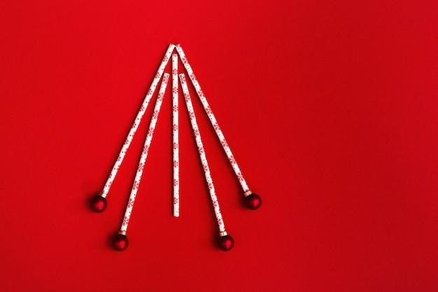 Árvore de natal criativa de canudos e bolas de ano novo no vermelho.