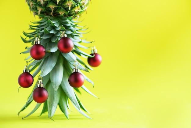 Árvore de natal criativa feita do abacaxi e da quinquilharia vermelha no fundo amarelo, espaço da cópia.