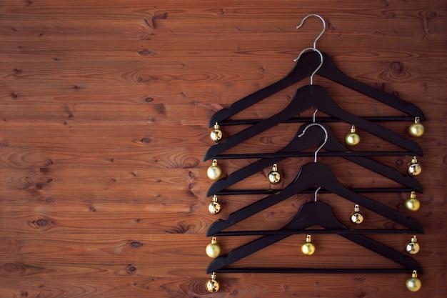 Árvore de natal de cabides. decorado com bolas de ouro. um concerto de vendas de natal.