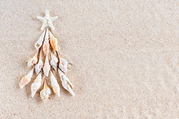 Árvore de natal de conchas e peixes-estrela em areia clara