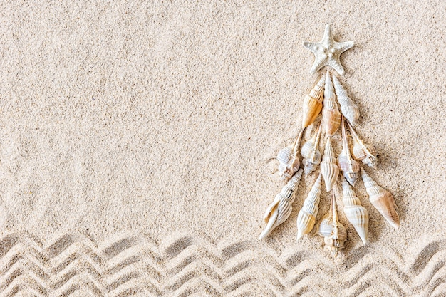 Árvore de natal de conchas e peixes-estrela em areia clara Foto Premium
