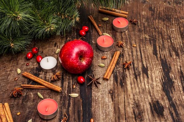 Árvore de natal de espírito, maçã fresca, canela, velas, cardamomo, anis estrelado. decorações da natureza, tábuas de madeira vintage