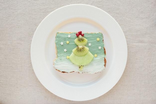Árvore de natal de frutas no café da manhã brinde creamcheese, divertido arte de comida para crianças