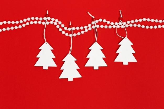 Árvore de natal de madeira branca pendurada em contas de pérolas de decoração.