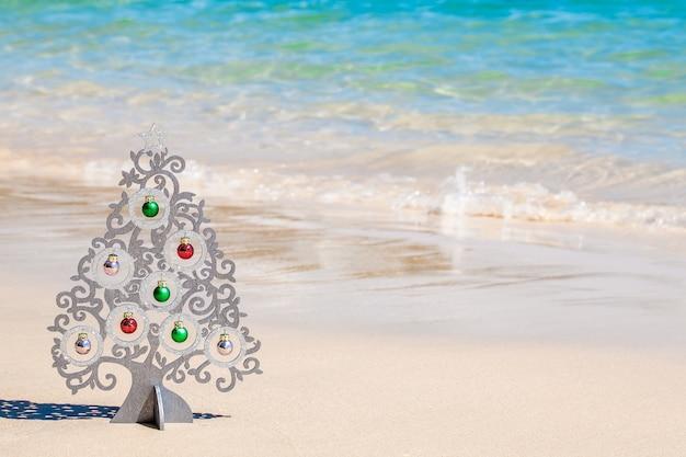 Árvore de natal de madeira com decorações na costa do mar, com areia branca e água azul clara
