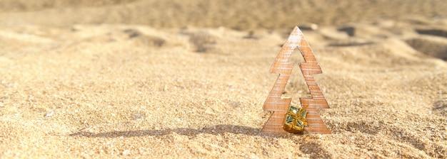 Árvore de natal de madeira de madeira em uma areia na praia tropical perto do oceano, verão natal