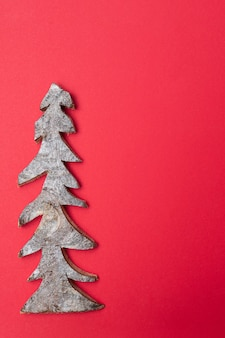 Árvore de natal de madeira em um fundo vermelho. cartão de natal.