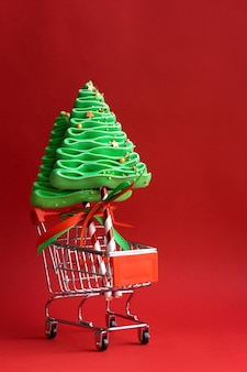 Árvore de natal de merengue em um carrinho de compras. doces de natal.