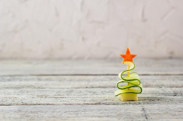 Árvore de natal de pepino e queijo com estrela de cenoura