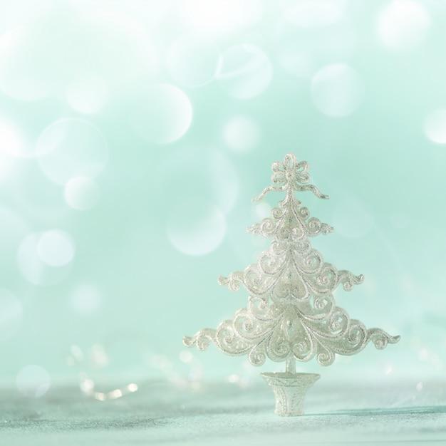 Árvore de natal de prata do glitter no fundo azul com bokeh das luzes, espaço da cópia.