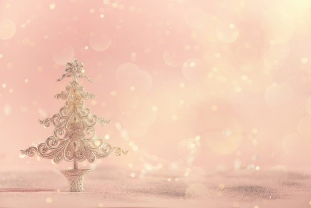 Árvore de natal de prata do glitter no fundo cor-de-rosa com bokeh das luzes, espaço da cópia.