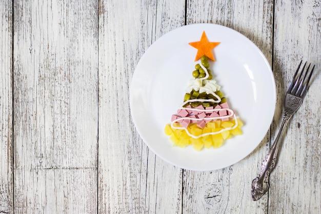Árvore de natal de uma salada de olivier em um prato