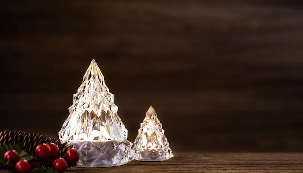 Árvore de natal de vidro com luzes na mesa de madeira escura com parede para chirstmas feliz e ano novo