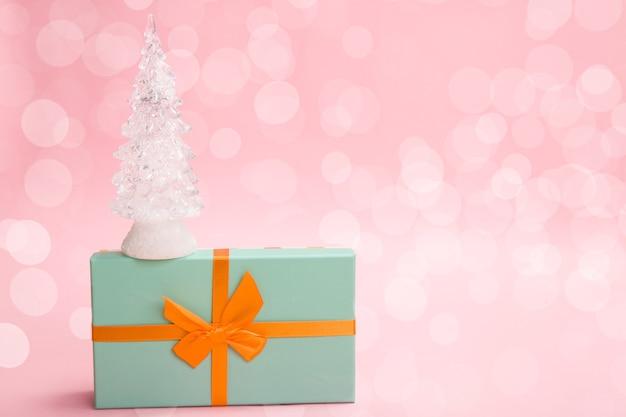 Árvore de natal de vidro em uma caixa verde com um laço laranja em um fundo rosa