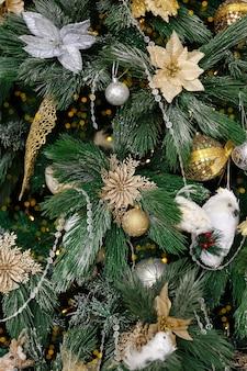 Árvore de natal decorada com bolas douradas e brinquedos em forma de flores