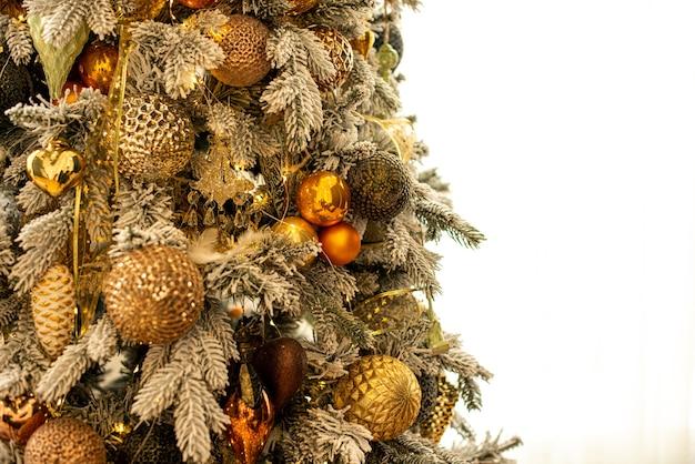Árvore de natal decorada com bolas douradas e brinquedos na sala de perto
