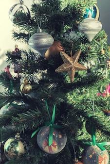 Árvore de natal decorada com enfeites, enfeites, bolhas, bolas e estrelas douradas