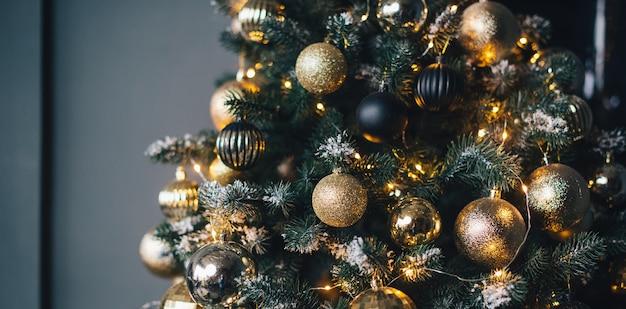 Árvore de natal decorada com guirlandas e bolas douradas em uma parede escura