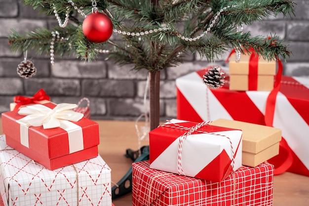 Árvore de natal decorada com lindos presentes vermelhos e brancos embrulhados em casa com parede de tijolo preto, conceito de design festivo, close-up.
