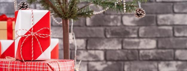 Árvore de natal decorada com lindos presentes vermelhos e brancos embrulhados em casa com parede de tijolo preto