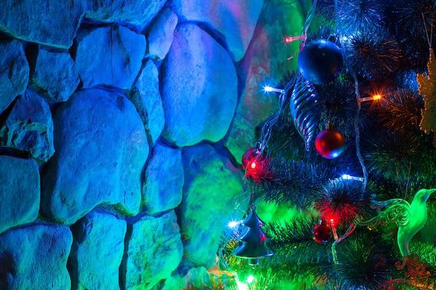 Árvore de natal decorada com luzes coloridas e brinquedos no fundo de um muro de pedra à noite