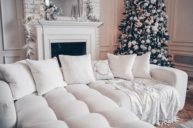Árvore de natal decorada com presentes no interior branco clássico da sala de estar