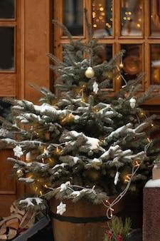 Árvore de natal decorada com uma guirlanda com flocos de neve de bolas de luz sob uma janela na rua