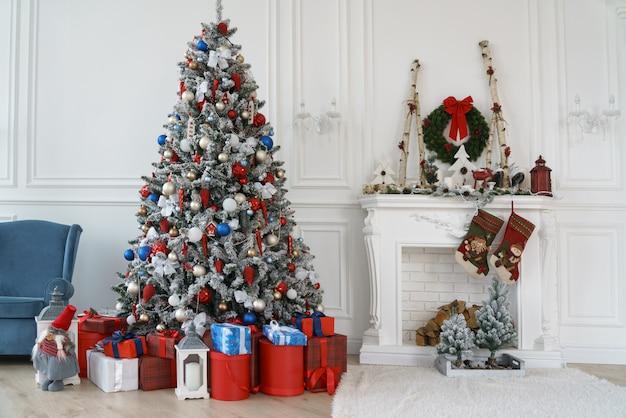 Árvore de natal decorada e caixas de presente vermelha ao lado da lareira branca decorada