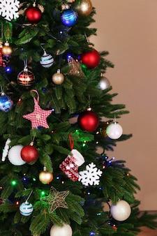 Árvore de natal decorada em parede marrom claro