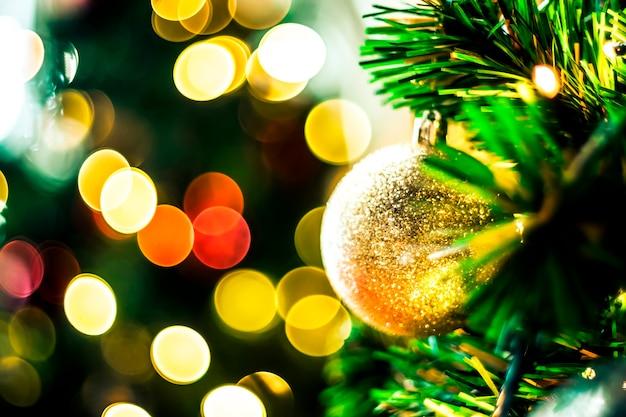 Árvore de natal decorada em plano de fundo multicolorido turva de ano novo. enfeite de natal em fundo de madeira com flocos de neve, cartão de feliz natal e feliz ano novo.
