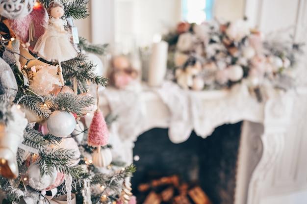 Árvore de natal decorada em suaves cores rosa no contexto da lareira clássica branca com decorações de natal.