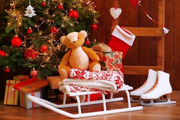 Árvore de natal decorada, escada e trenó na parede de madeira